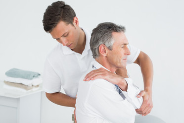Chiropractor assesing middle aged male patient's thoracic spine