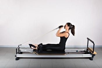 woman using pilates reformer for rehabilitation