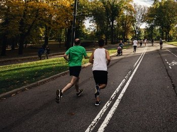 two men jogging through a park on a sunny day